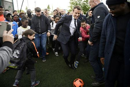 Emmanuel Macron (C), head of the political movement En Marche !, or Onwards !, and candidate for the 2017 presidential election, kicks a soccer ball during a campaign visit in Sarcelles, near Paris, April 27, 2017.  REUTERS/Martin Bureau/Pool