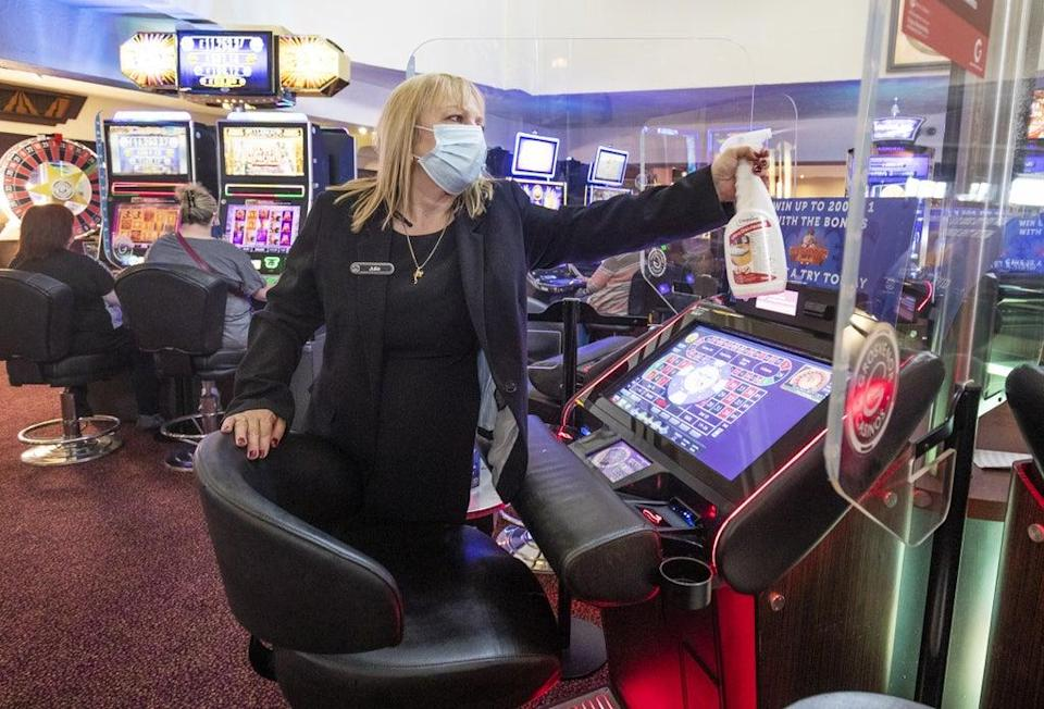 Electronic gaming manager Julie Baxter cleans the screens at the Grosvenor Edinburgh Maybury Casino after opening on May 17 (Jane Barlow/PA) (PA Wire)