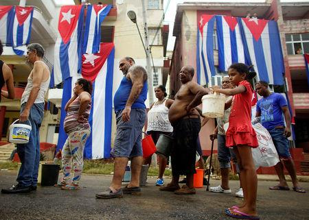 People line up for potable water from a government-run water tanker (not pictured) next to Cuban flags hung up to dry after Hurricane Irma caused flooding and a blackout, in Havana, Cuba September 11, 2017. REUTERS/Alexandre Meneghini