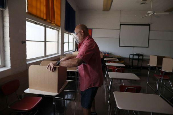PHOTO: School principal Frank Loya Jr. sets up social distancing dividers for students in a classroom at St. Benedict School, amid the outbreak of the coronavirus disease, in Montebello, Calif., near Los Angeles, on July 14, 2020. (Lucy Nicholson/Reuters)
