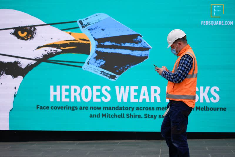 An essential worker wearing a face mask walks past a 'Heroes Wear Masks' sign in Melbourne, the first city in Australia to enforce mask-wearing to curb a resurgence of COVID-19