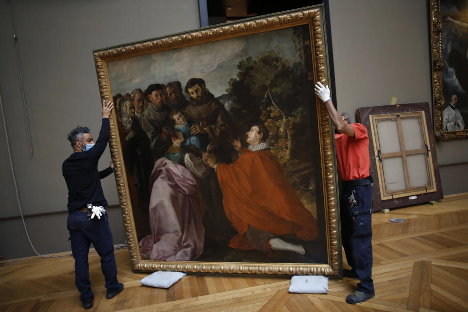 Workers handle the painting called 'The Healing of Saint Bonaventure as a Child by Saint Francis' by Spanish painter Francisco de Herrera, in the Louvre museum, in Paris, Tuesday, Feb. 9, 2021. The forced closure has granted museum officials a golden opportunity to carry out long-overdue refurbishments that were simply not possible with nearly 10 million visitors a year. (AP Photo/Thibault Camus)