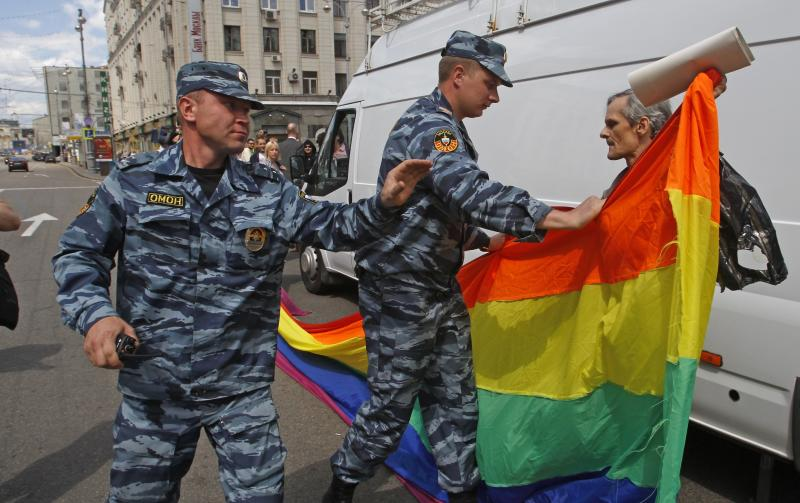Russian police officers detain a gay rights activist with his flag during an attempt to hold a gay pride parade in Moscow, Russia, Sunday, May 27, 2012. Russian police have detained around a dozen protesters demanding the right to hold a gay pride parade in Moscow. Activists have long petitioned the government for permission to stage such a parade, but have always been denied. (AP Photo/Mikhail Metzel)