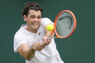 Taylor Fritz of the US plays a return to Steve Johnson of the US during the men's singles second round match on day four of the Wimbledon Tennis Championships in London, Thursday July 1, 2021. (AP Photo/Kirsty Wigglesworth)