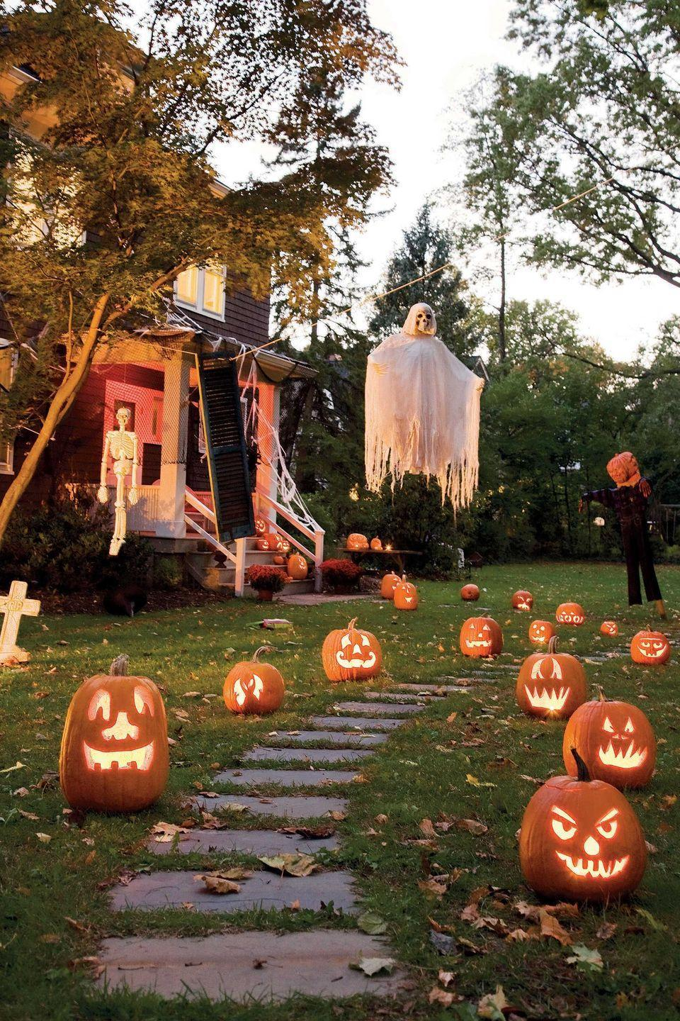 """<p>Hanging ghosts and skeletons greet trick or treaters as they make their way up the path.</p><p><strong>RELATED: </strong><a href=""""https://www.womansday.com/style/fashion/g490/20-clever-last-minute-costume-ideas/"""" rel=""""nofollow noopener"""" target=""""_blank"""" data-ylk=""""slk:Last-Minute Halloween Costume Ideas You Can Whip Up at Home"""" class=""""link rapid-noclick-resp"""">Last-Minute Halloween Costume Ideas You Can Whip Up at Home</a></p>"""