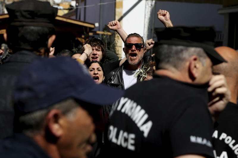 Turkish Cypriot demonstrators behind the Greek Cypriots riots police, shout slogans during a protest against a closed crossing point in the ethnically divided capital Nicosia, Cyprus, Saturday, March 7, 2020. Demonstrators staged another protest against a decision by the Cyprus government to temporarily shut four of nine crossing points along a United Nations controlled buffer zone that separates the south from the breakaway Turkish Cypriot north. The Cypriot government says it shut the crossing points to better check for potential coronavirus carriers. (AP Photo/Petros Karadjias)