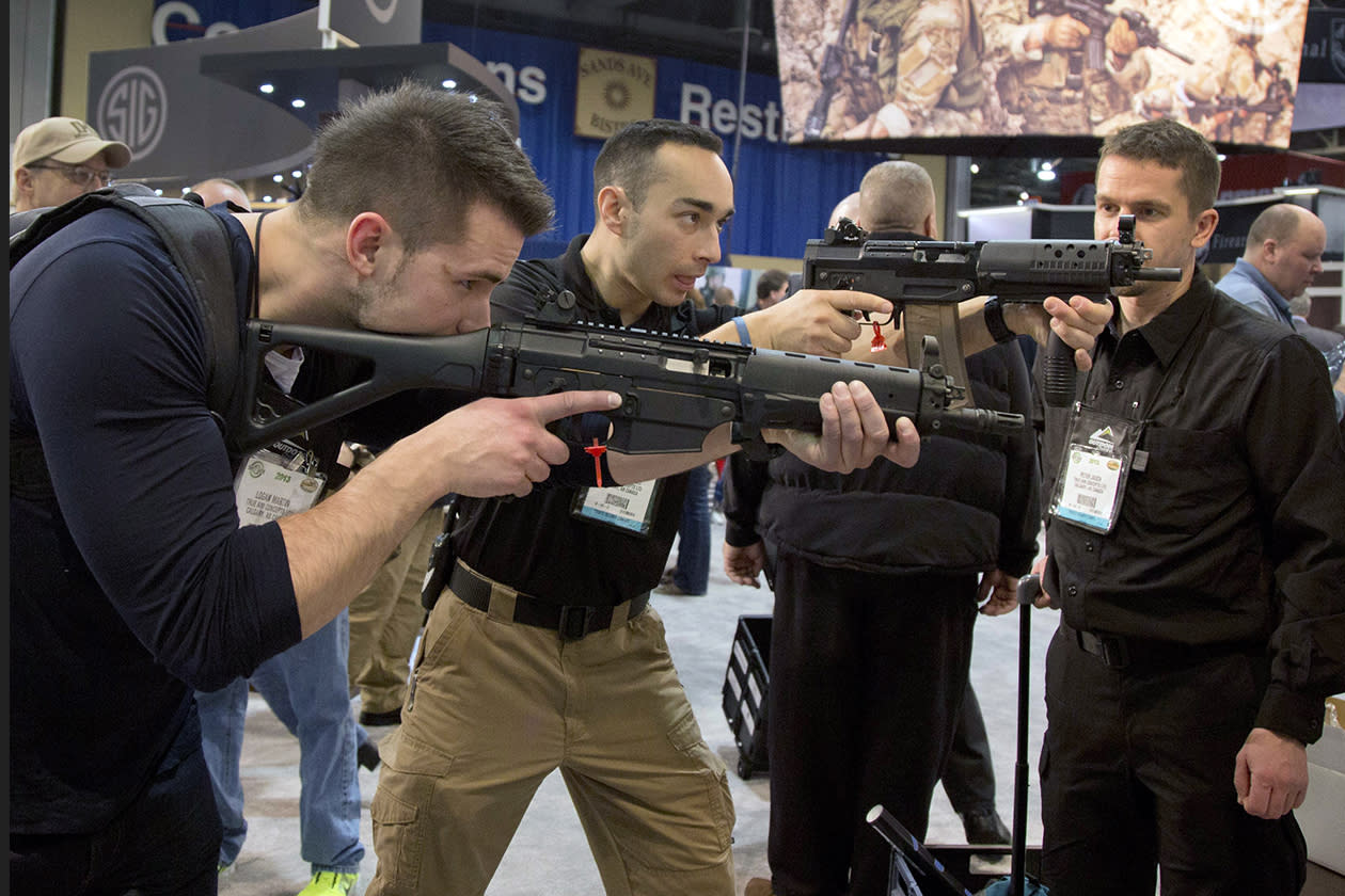 Firearms instructors Logan Martin, left, and Andres Gonzalez, of Calgary, Alberta, look through the sights of Sig Sauer Swat Patrol AR rifles.