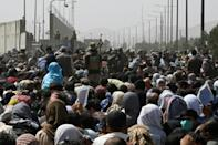 Afghans gather on a roadside near the military part of the airport in Kabul on August 20, 2021, hoping to flee from the country after the Taliban's military takeover