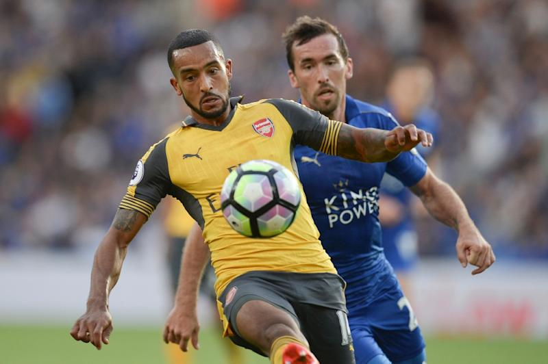Arsenal's midfielder Theo Walcott (L) tries to hold off Leicester City's defender Christian Fuchs on August 20, 2016