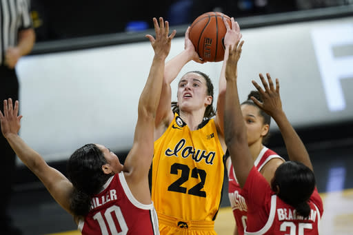Iowa guard Caitlin Clark (22) drives to the basket between Ohio State guard Braxtin Miller (10) and forward Tanaya Beacham, right, during the first half of an NCAA college basketball game, Wednesday, Jan. 13, 2021, in Iowa City, Iowa. (AP Photo/Charlie Neibergall)