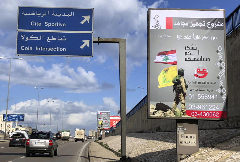 """FILE - This January 19, 2018 file photo, shows a billboard from Hezbollah's committee for the support of the Islamic resistance, with a Hezbollah fighter holding the group's yellow banner and Lebanon's national flag, in southern Beirut, Lebanon. The Trump administration has been imposing sanctions on Hezbollah and institutions linked to it at an unprecedented rate in recent months, targeting lawmakers in Lebanon's parliament for the first time, as well as a local bank that Washington claims has ties to the group. Arabic on the poster reads, """"A project to equip a holy warrior, He who equips an invader is part of the battle (a saying from Islam's Prophet Muhammad), and we thank you for your contribution, bottom."""" (AP Photo/Hussein Malla, File)"""