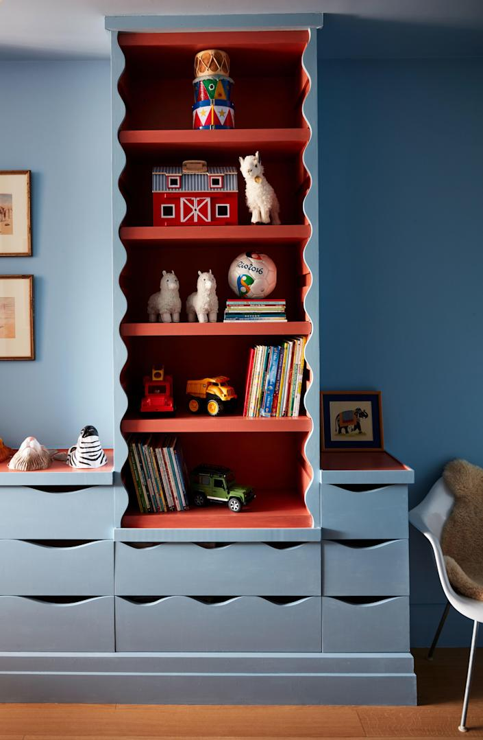 Valle used the wavy edge motif from the living room for the shelves and drawers in his son's room, painted in Farrow & Ball's Lulworth Blue.