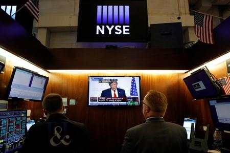 Traders watch monitors displaying a media conference with U.S. President Donald Trump live at the G7 summit on the trading floor at the New York Stock Exchange (NYSE) in New York City