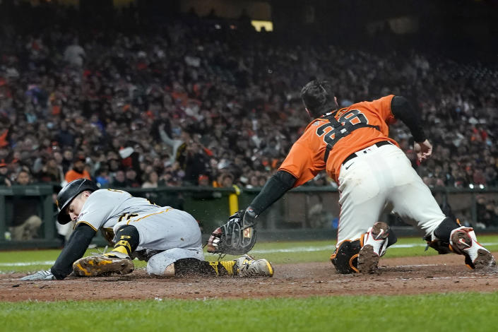 Pittsburgh Pirates' Adam Frazier, left, scores past San Francisco Giants catcher Buster Posey during the seventh inning of a baseball game in San Francisco, Friday, July 23, 2021. (AP Photo/Jeff Chiu)