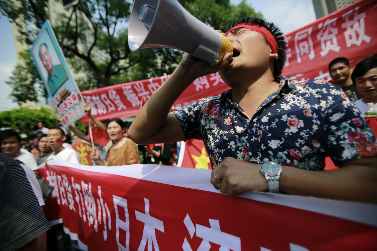 Protesters shout anti-Japan slogans near the Japanese Consulate General Tuesday, Sept. 18, 2012, in Shanghai, China. The 81st anniversary of a Japanese invasion brought a fresh wave of anti-Japan demonstrations in China on Tuesday, with thousands of protesters venting anger over the colonial past and a current dispute involving contested islands in the East China Sea. (AP Photo/Eugene Hoshiko)