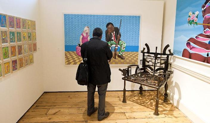 A visitor stands next to a chair designed by Mozambican artist Concalo Mabunda displayed at the Contemporary African Art Fair at Somerset House in London on October 15, 2013 (AFP Photo/Will Oliver)