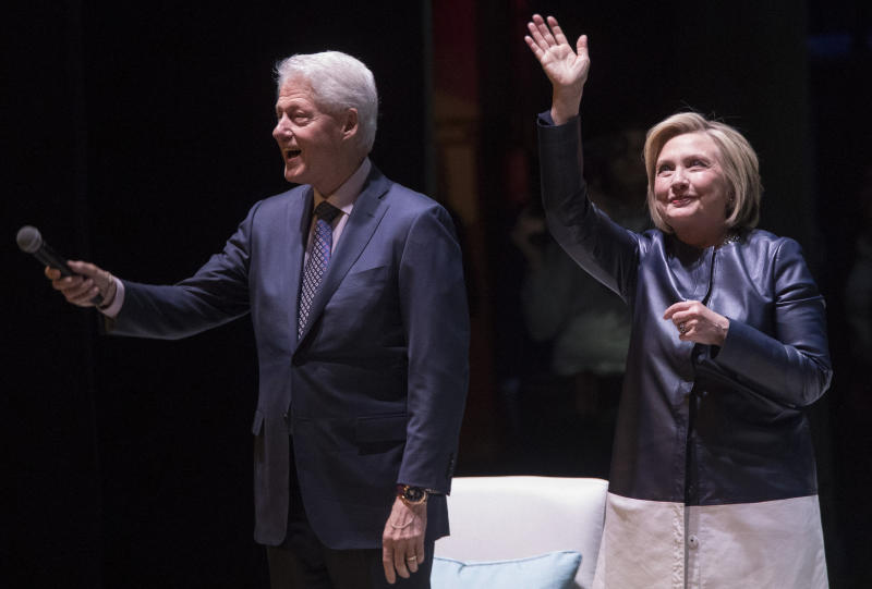 """Former President Bill Clinton and former Secretary of State Hillary Clinton wave at the crowd as they arrive on stage Thursday night for """"An Evening With the Clintons"""" at the Beacon Theatre in New York."""