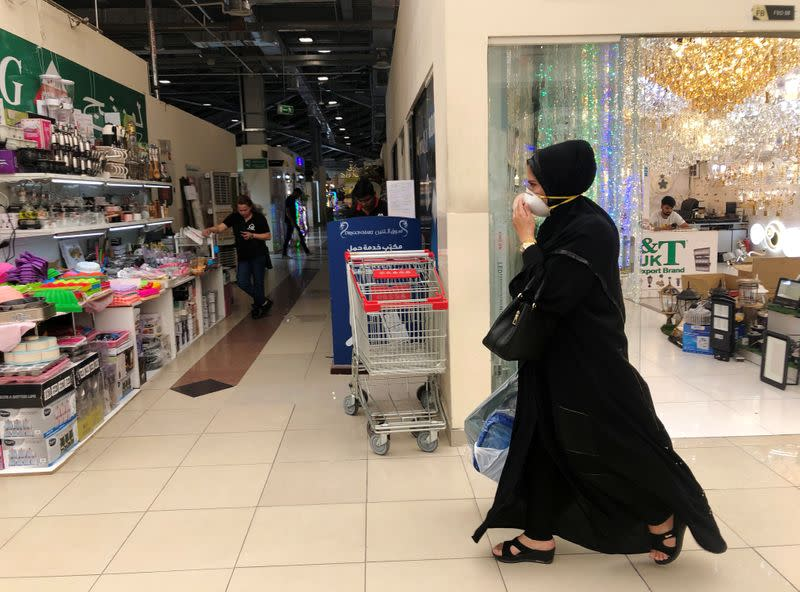A woman wears a protective face mask, following the outbreak of the new coronavirus, as she walks at Dragon Mart, a Chinese themed discount shopping centre, in Dubai