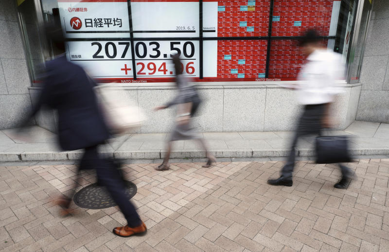 People walk past an electronic stock board showing Japan's Nikkei 225 index at a securities firm in Tokyo Wednesday, June 5, 2019. Shares surged Wednesday in Asia following a rally on Wall Street spurred by signs the Federal Reserve is ready to cut interest rates to support the U.S. economy against risks from escalating trade wars.(AP Photo/Eugene Hoshiko)