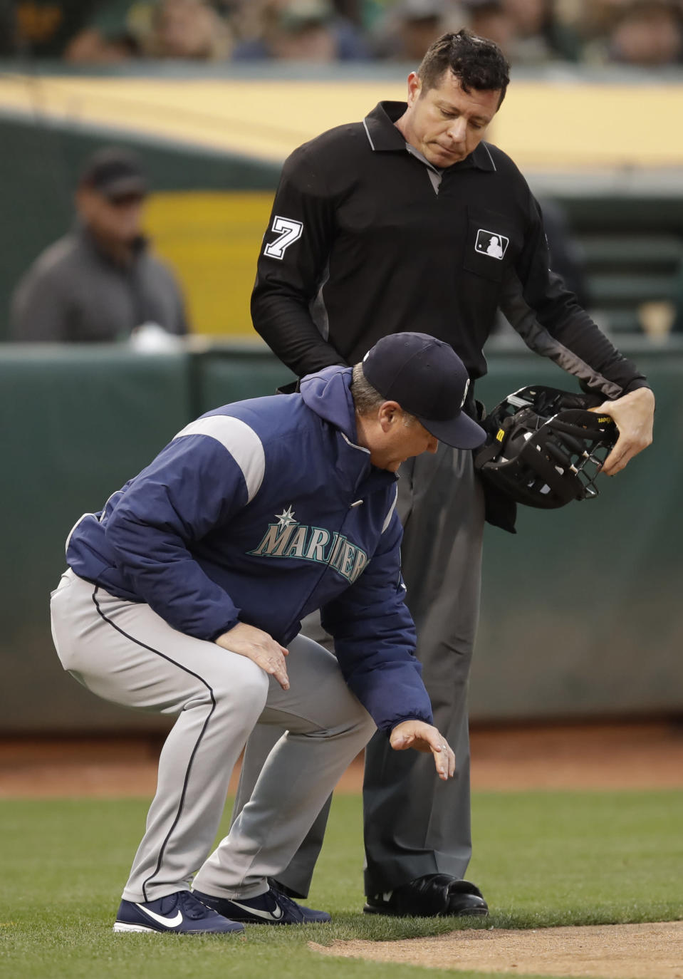 Seattle Mariners manager Scott Servais, left, squats at home plate as he speaks with umpire Carlos Torres in the fourth inning of a baseball game against the Oakland Athletics, Saturday, June 15, 2019, in Oakland, Calif. Servais was ejected from the game by Torres. (AP Photo/Ben Margot)