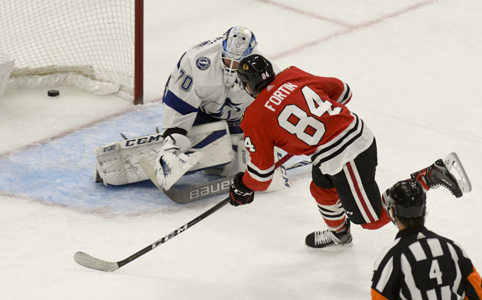 Chicago Blackhawks left wing Alexandre Fortin (84) scores a goal past Tampa Bay Lightning goaltender Louis Domingue (70) during the first period of an NHL hockey game on Sunday Oct. 21, 2018, in Chicago. (AP Photo/Matt Marton)