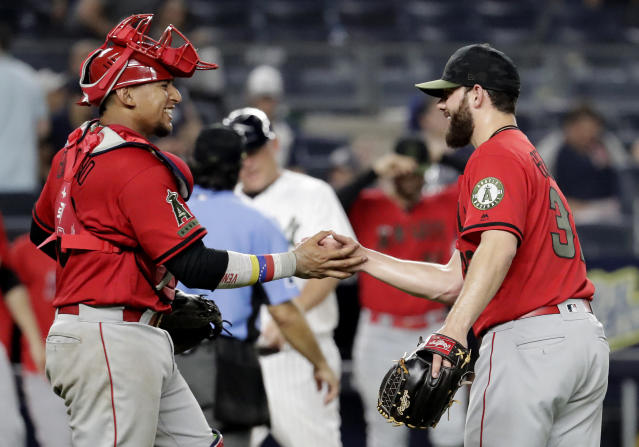 Los Angeles Angels catcher Jose Briceno, left, and relief pitcher Cam Bedrosian celebrate after the Angels defeated the New York Yankees 11-4 in a baseball game Saturday, May 26, 2018, in New York. (AP Photo/Julio Cortez)