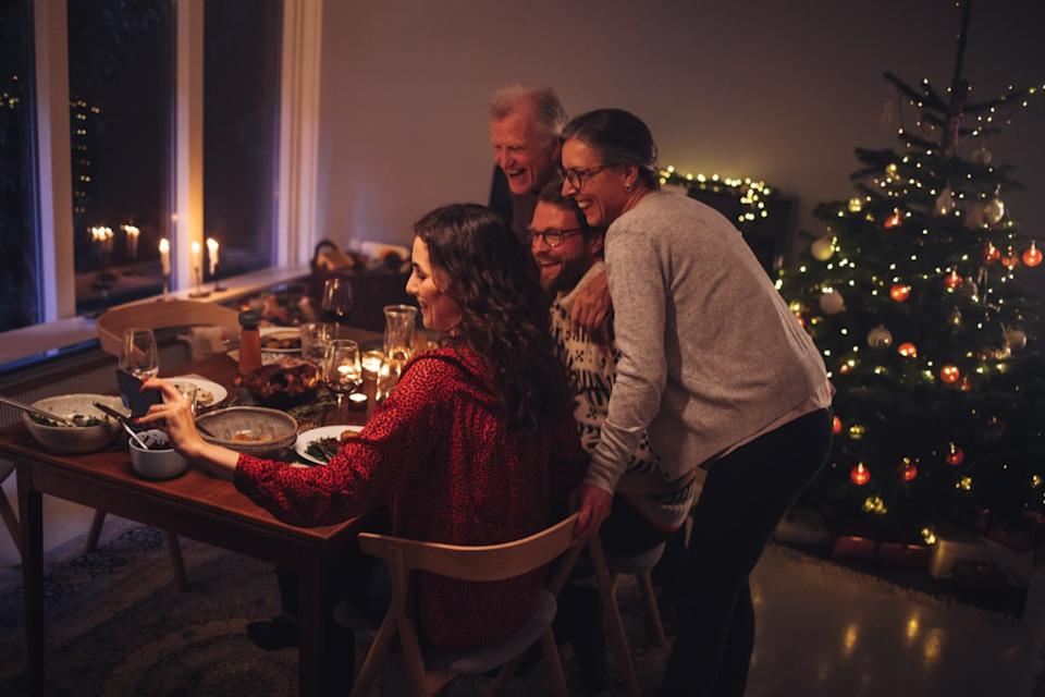 Four people at a table in front of a Christmas tree and one woman holding a phone