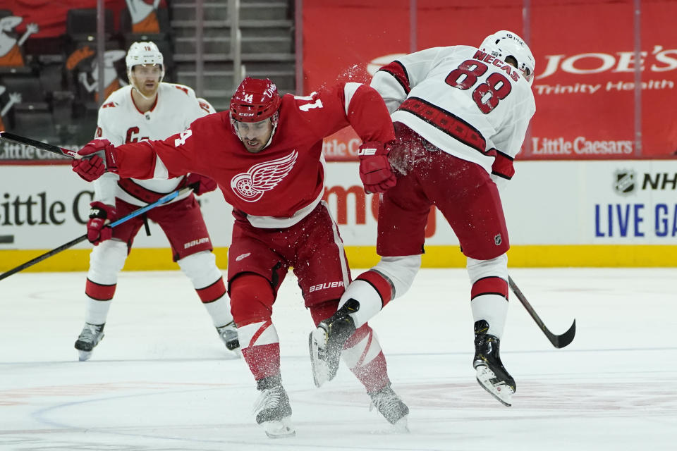 Detroit Red Wings center Robby Fabbri (14) and Carolina Hurricanes center Martin Necas (88) collide in the third period of an NHL hockey game Saturday, Jan. 16, 2021, in Detroit. (AP Photo/Paul Sancya)