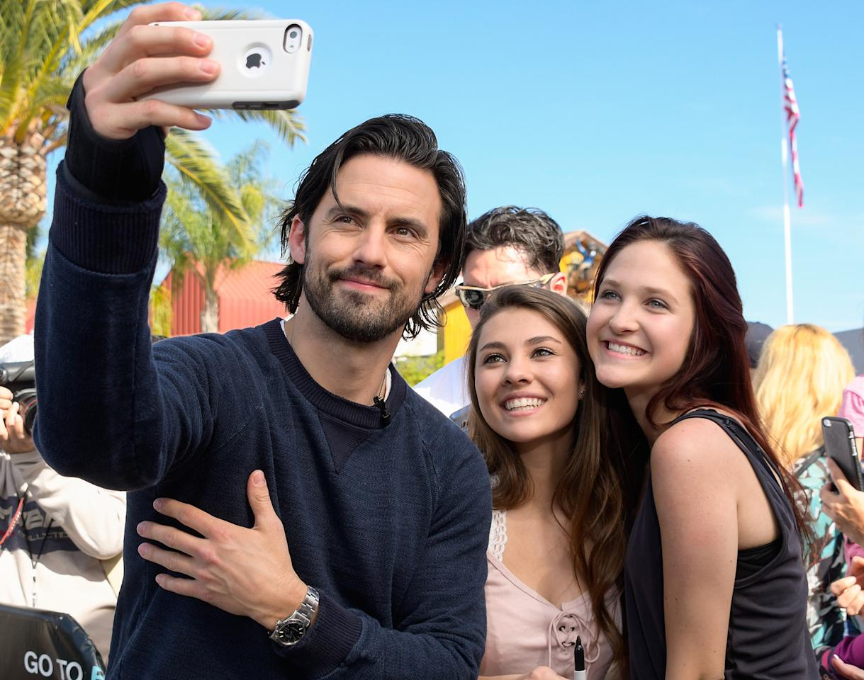 Milo Ventimiglia takes a selfie with fans while on the Extra set in Universal City, California, on Wednesday.