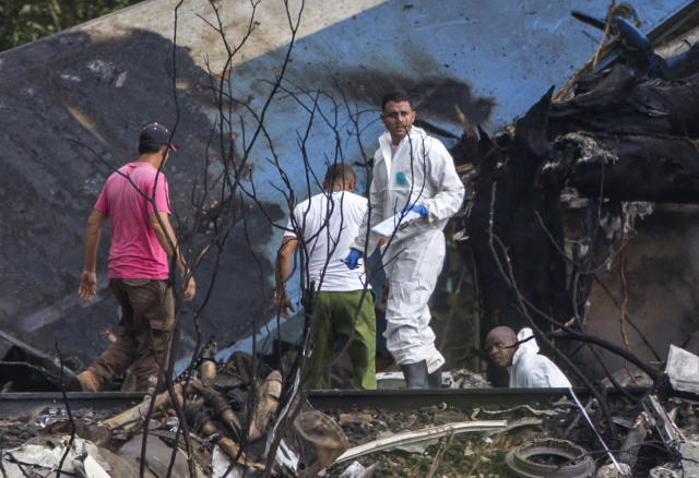 <p>Forensic investigators and Ministry of Interior officers sift through the remains of a Boeing 737 that plummeted into a yuca field with more than 100 passengers on board, in Havana, Cuba, Friday, May 18, 2018. (Photo: Desmond Boylan/AP) </p>