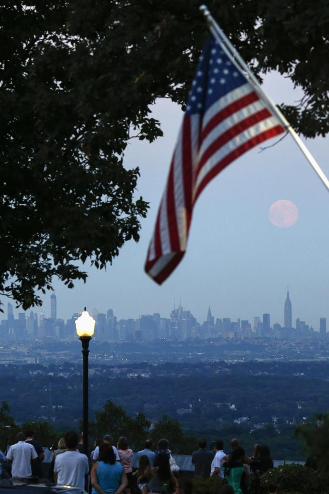 """People watch a full moon known as a """"supermoon"""" while it rises over the skyline of New York and the Empire State Building, as seen from the Eagle Rock Reservation in West Orange, New Jersey, August 10, 2014. The astronomical event occurs when the moon is closest to the Earth in its orbit, making it appear much larger and brighter than usual. REUTERS/Eduardo Munoz (UNITED STATES - Tags: ENVIRONMENT SOCIETY)"""
