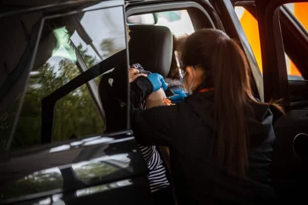 Health-care workers provide COVID-19 vaccines at a drive-thru clinic in Central Park in Burnaby, B.C., on March 26.  (Ben Nelms/CBC - image credit)