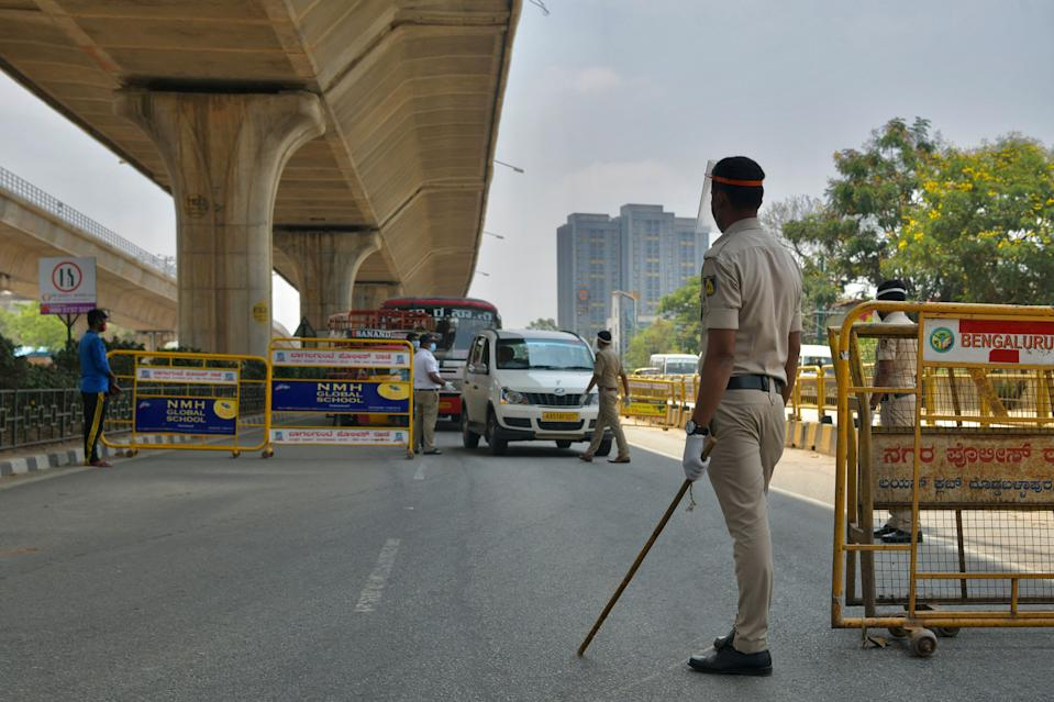 Police personnel conduct checks on commuters at a temporary check post during the weekend lockdown imposed as a preventive measure against the spread of the Covid-19 coronavirus in Bangalore on April 24, 2021. (Photo by Manjunath Kiran / AFP) (Photo by MANJUNATH KIRAN/AFP via Getty Images)
