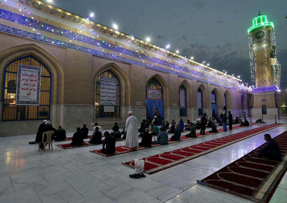 FILE - In this Saturday, April 10, 2021, file photo, Muslims perform evening prayer at the Sunni shrine of Abdul-Qadir al-Gailani, ahead of the upcoming Muslim fasting month of Ramadan, in Baghdad, Iraq. Muslims are facing their second Ramadan in the shadow of the pandemic. Many Muslim majority countries have been hit by an intense new coronavirus wave. While some countries imposed new Ramadan restrictions, concern is high that the month's rituals could stoke a further surge. (AP Photo/Khalid Mohammed, File)