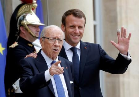 FILE PHOTO: French President Emmanuel Macron accompanies Tunisia's President Beji Caid Essebsi after an international conference on Libya at the Elysee Palace in Paris