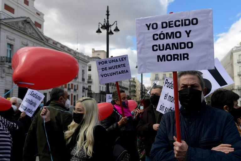 """A man holds a placard reading """"I decide when and how to die"""" during a demonstration in support of the law legalising euthanasia"""