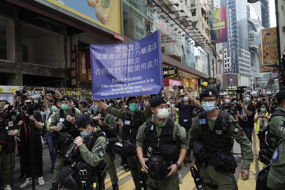 A police officer displays a warning banner on China's National Day in Causeway Bay, Hong Kong, Thursday, Oct. 1, 2020. A popular shopping district in Causeway Bay saw a heavy police presence on the Oct. 1 National Day holiday despite low protester turnout. (AP Photo/Kin Cheung)