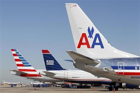 The tail sections of a newly designed American Airlines aircraft, a US Airways aircraft and a traditional American Airlines aircraft are lined up at at Dallas-Ft Worth International Airport