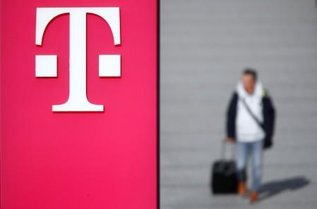 A man walks past the logo of Deutsche Telekom AG at the headquarters of German telecommunications giant in Bonn