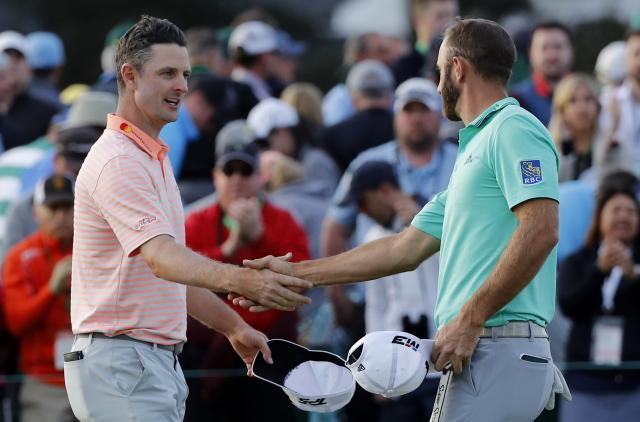 Justin Rose of England (L) shakes hands with Dustin Johnson of the U.S. on the 18th green as they finished first round play at the 2018 Masters golf tournament at the Augusta National Golf Club in Augusta, Georgia, U.S. April 5, 2018. REUTERS/Mike Segar