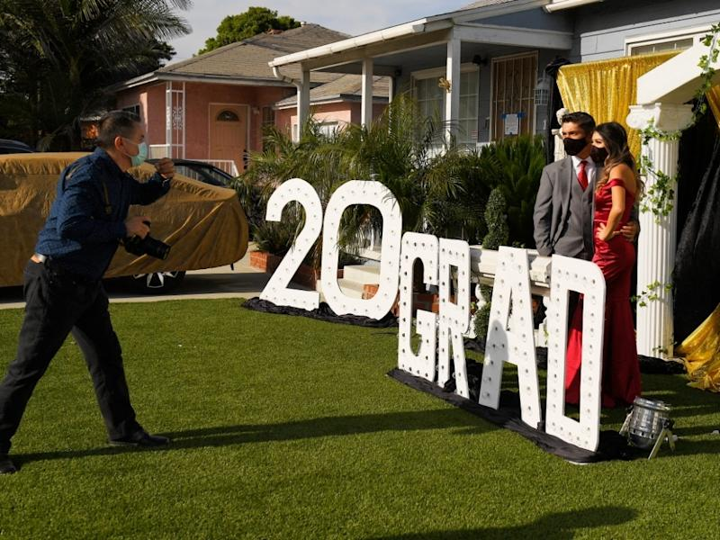 Gabriel Lopez, center, and Delilah Santos, right, have their pictures and video taken by Philippe Michel in front of the home of Diane Scott during the coronavirus outbreak, Saturday, May 16, 2020, in Los Angeles.