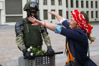 A woman embraces a soldier guarding the Belarusian Government building, in an exaggerated show of friendliness, in Minsk, Belarus, Friday, Aug. 14, 2020. Some thousands of people have gathered in the centre of the Belarus capital, Minsk, in a show of anger over a recent brutal police crackdown on peaceful protesters that followed a disputed presidential election. (AP Photo/Sergei Grits)