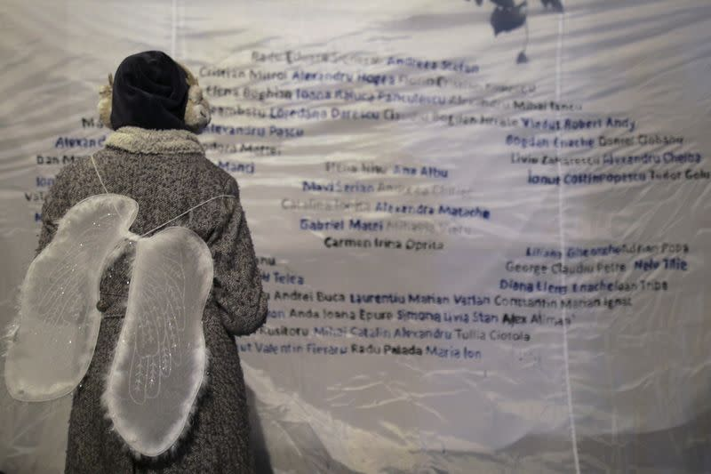 A girl wearing angel wings looks at a poster that features the names of the 65 people that died during or in the aftermath of the fire at Colectiv Club on October 30, 2015, during an event that commemorated the victims
