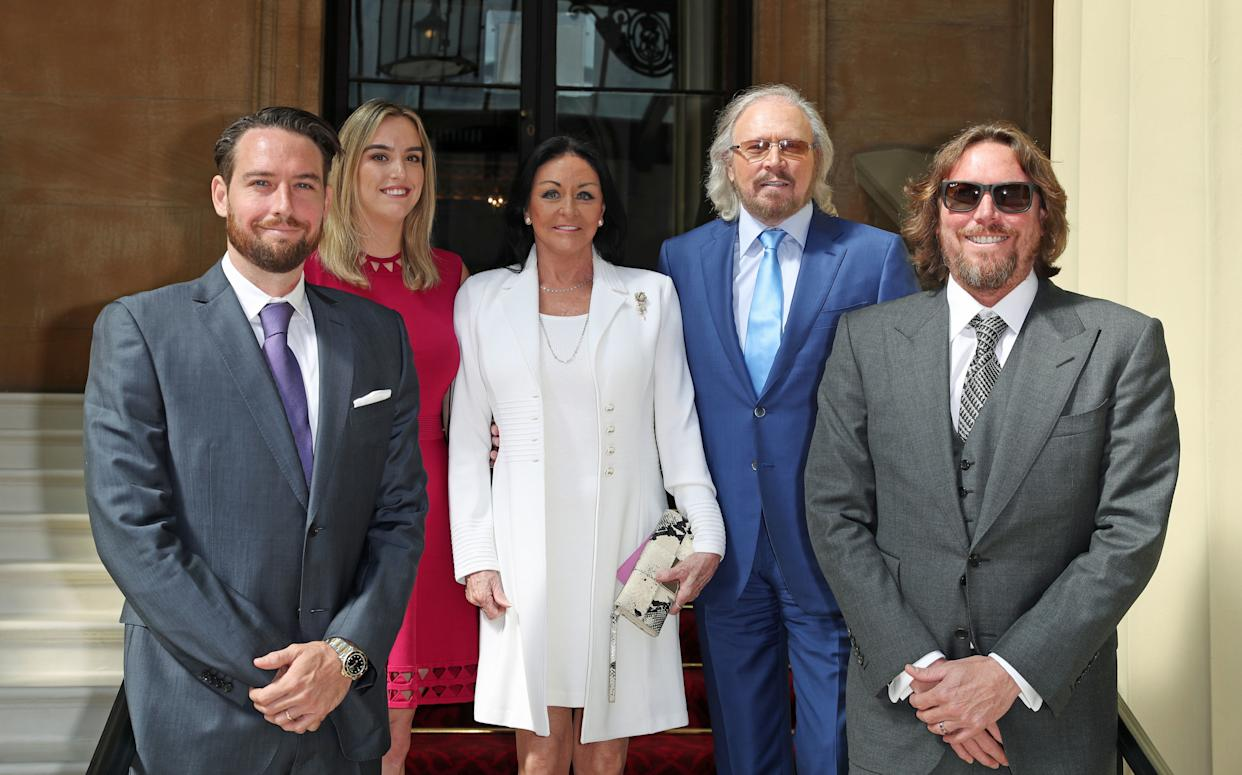 LONDON, ENGLAND - JUNE 26: Singer and songwriter Barry Gibb (2R) poses for a photo with his wife Linda, and children, Michael, Alexandra and Ashley ahead of being knighted during an investiture ceremony at Buckingham Palace on June 26, 2018 in London, England. (Photo by Steve Parsons - WPA Pool/Getty Images)