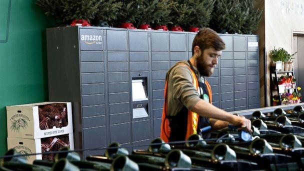 PHOTO: An employee organizes shopping carts in front of a wall of Amazon.com Inc. lockers, a self-service parcel delivery service, inside the Lakeview Whole Foods Market Inc. store in Chicago, Nov. 20, 2017. (Daniel Acker/Bloomberg via Getty Images, FILE)