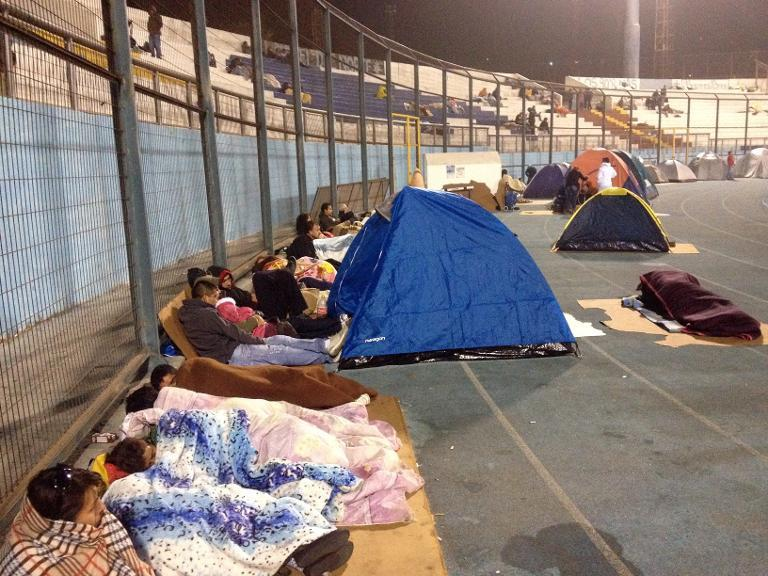 Locals take refuge at the city stadium following a tsunami alert after a powerful 8.2-magnitude earthquake hit off Chile's Pacific coast, on April 2, 2014 in Iquique