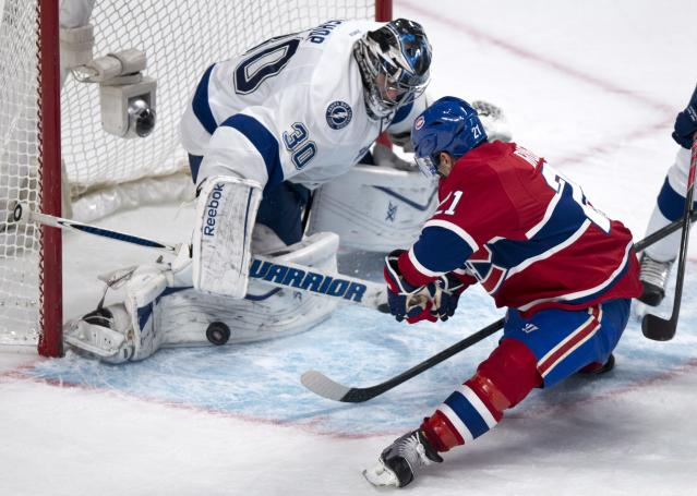 Tampa Bay Lightning goalie Ben Bishop stops Montreal Canadiens' Brian Gionta during the third period of an NHL hockey game Tuesday, Nov. 12, 2013, in Montreal. The Lightning won 2-1 in a shootout. (AP Photo/The Canadian Press, Paul Chiasson)