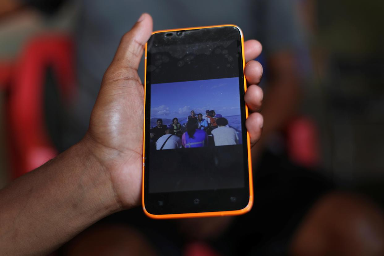 A friend of Maroly Bastardo shows a picture of the boat that Bastardo and her family boarded, in Guiria, Venezuela, on May 24. (Photo: Ivan Alvarado/Reuters)