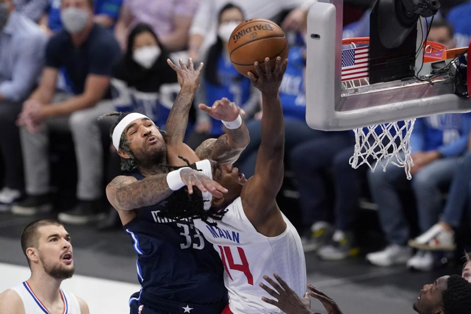 Dallas Mavericks center Willie Cauley-Stein (33) fouls Los Angeles Clippers guard Terance Mann (14) on a shot attempt in the first half in Game 3 of an NBA basketball first-round playoff series in Dallas, Friday, May 28, 2021. (AP Photo/Tony Gutierrez)