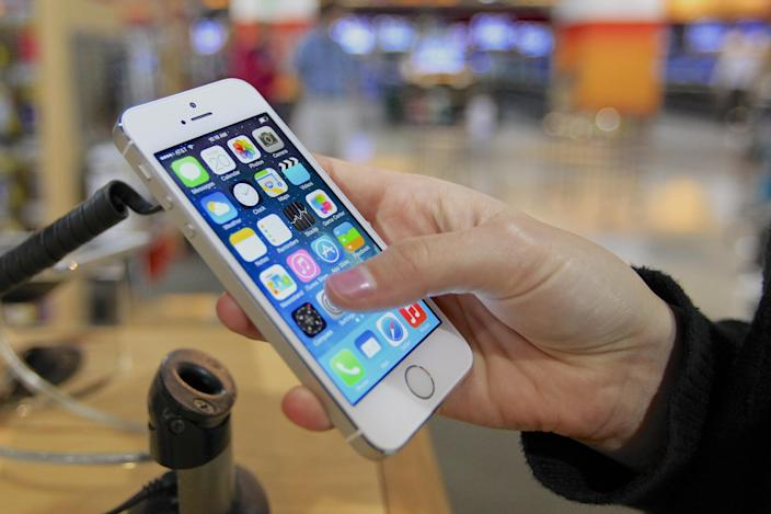 A customer examines a new iPhone 5s at the Nebraska Furniture Mart in Omaha, Neb., on Friday, Sept. 20, 2013, the day the new iPhone 5c and 5s models go on sale. (AP Photo/Nati Harnik)